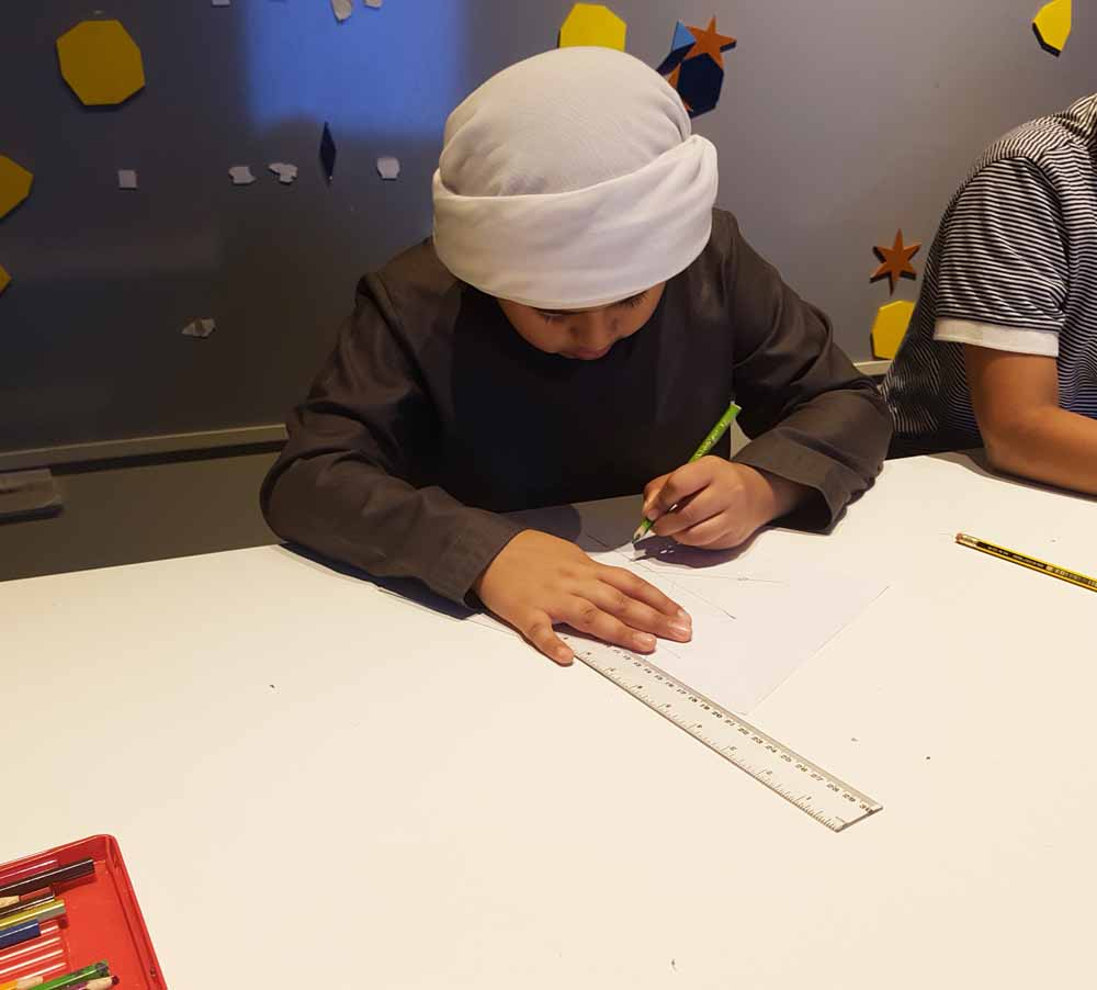Boy in the UAE drawing an Islamic geometric pattern in a workshop by Eric Broug