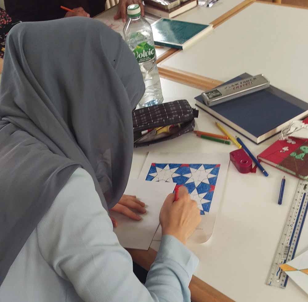 Muslim girl drawing an Islamic geometric pattern in a workshop by Eric Broug